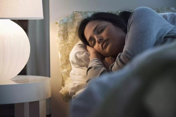 Lâmpada que ilumina a mulher latino-americano de sono