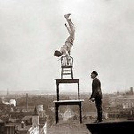 Man Balancing on a Chair on a Building