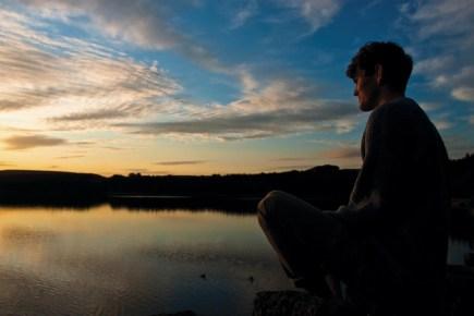 Man Meditating by a Lake