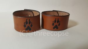 leather cuff with a wolf paw motif picked out in black with a light tan finnish