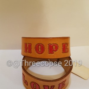 a leather cuff stamped with the word hope and painted in with acrylic