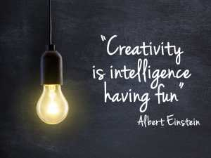 Light bulb lamp on blackboard background with creativity quote