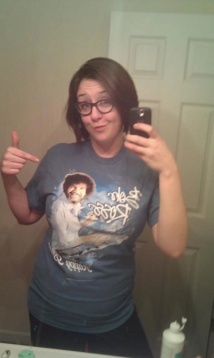 brunette girl wearing a bob ross shirt
