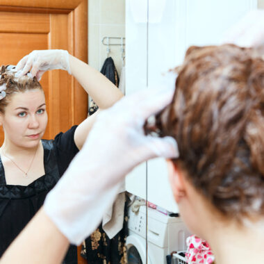 woman dying hair at home in front of mirror