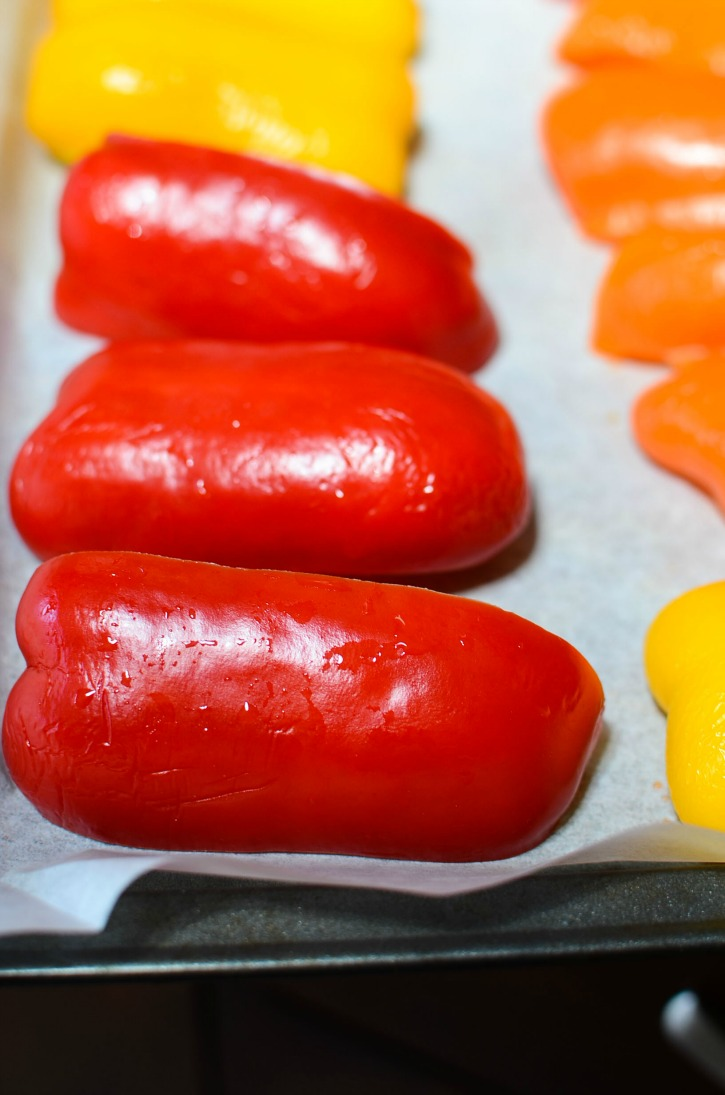 sliced peppers on parchment paper on baking sheet