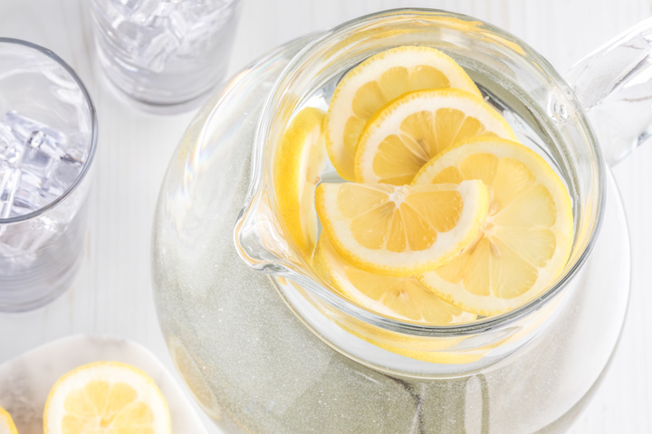 A top down view of a pitcher of lemon water with lemon slices ready for drinking.