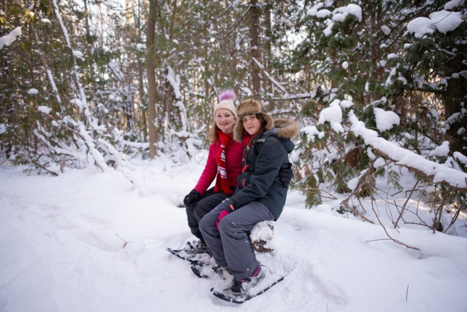 mother_daughter_seated_in_woods_wearing_snowshoes