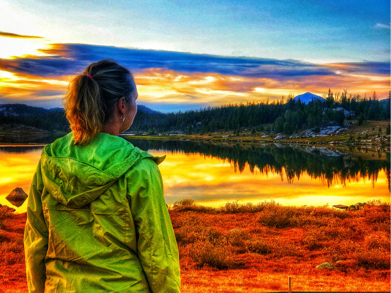 woman staring out at sunset over alpine lake on beartooth highway in Montana
