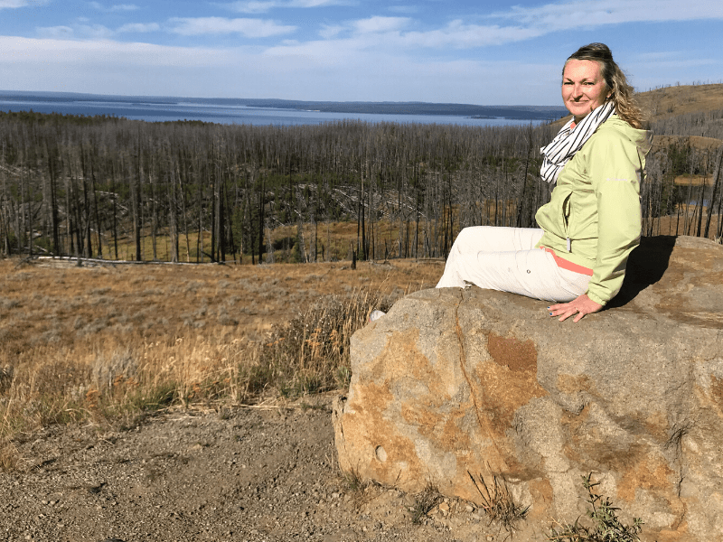 woman in green jacket sitting on a rock looking out at Yellowstone Lake in Yellowstone National Park on a group travel tour