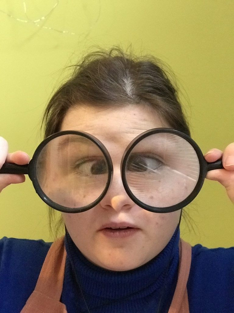 silly_young_teen_using_two_magnifying_glasses_for_eye_glasses