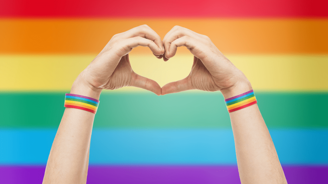 rainbow_flag_behind_hands_making_heart_sign