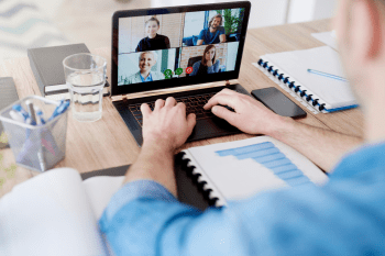 man on a group video conference on laptop