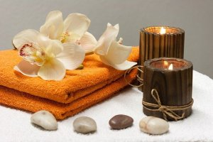 White towel topped with 4 small stones in a line (2 white, 1 gray, 1 brown) with a short and tall candle with wooden holders on the right. 2 orange towels topped with white flowers on the left.