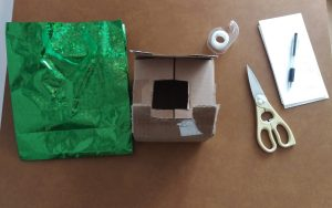 Supplies to make Positivity Affirmation Box: Green, gift bag, cardboard box, scissors, tape, paper and pen.