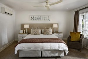 Clean and organized bedroom (white and brown themed) with night stand on either side and painting overhead