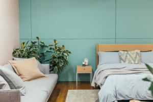 Bedroom with blue walls and plant and sofa on left, bed on right.