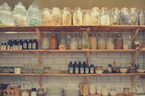Pantry shelving with spices and herbs in glass jars.