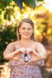 Woman hold in hands the bottle of essential oil