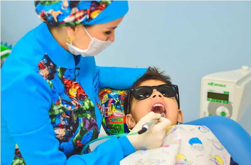 a dentist attending to a child