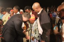 Bishop Steven ministering at a prayer line during a crusade meeting.