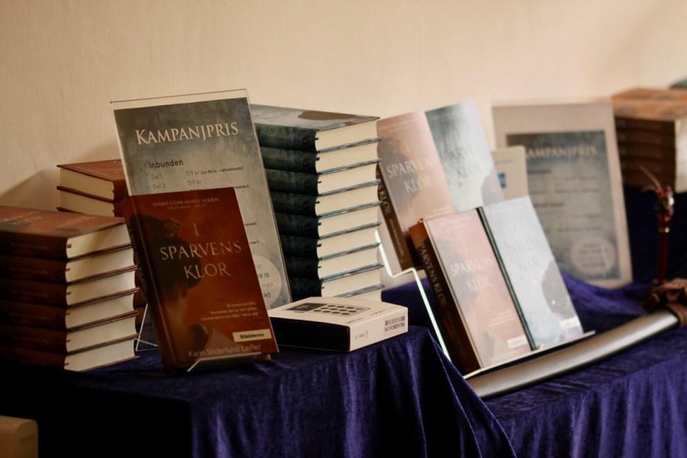 """bord med böcker i högar vid boksläpp av """"I Sparvens klor"""""""