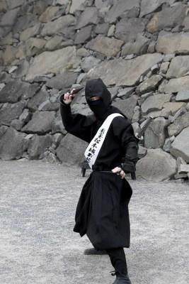man in ninjakläder framför stengrund