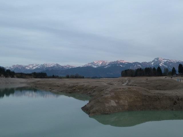 Alpenglühen hinter dem Forggensee ohne Wasser