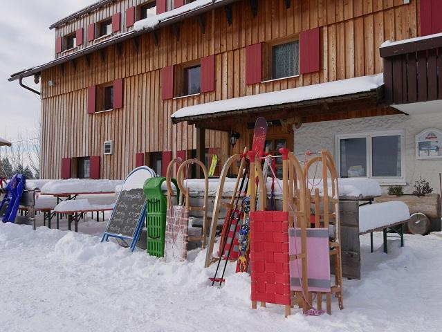 Buronhütte im Winter mit Schlitten und Skiern