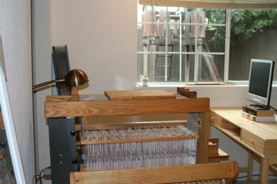 The loom and bench in the new weaving studio.  Barely visible in the right side is the computer desk for the computer that will drive the loom (and also be my home office when I'm working).