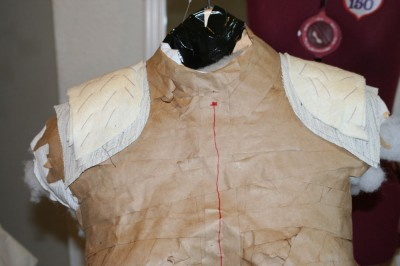Shoulder pads, completed and sewn together, steam pressed on the dress form so they'll hold their shape.