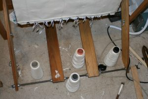 Cones of yarn on the floor, directly under the beater.  (Please ignore the mess.)
