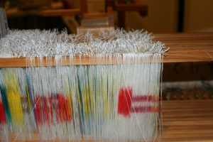 Warp yarns passing over the shafts on the way to the back of the loom.