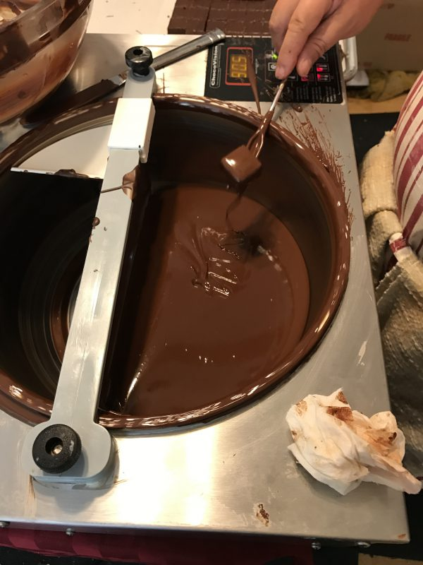 removing excess chocolate from a freshly-dipped bonbon