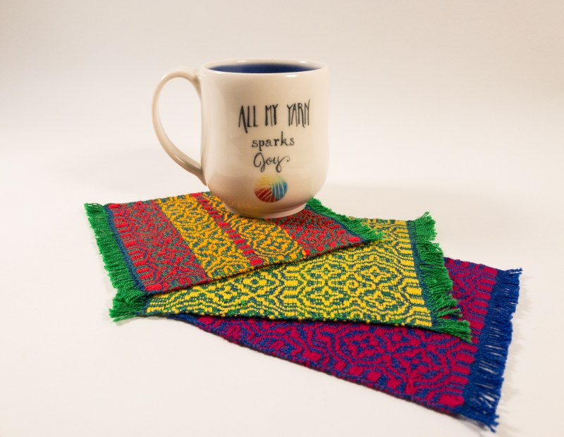 """All my yarn sparks joy"" mug on three mug rugs"