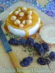 Wheel of brie cheese with hardened toffee and hazelnuts ured over the top and tumbling down the sides of the cheese