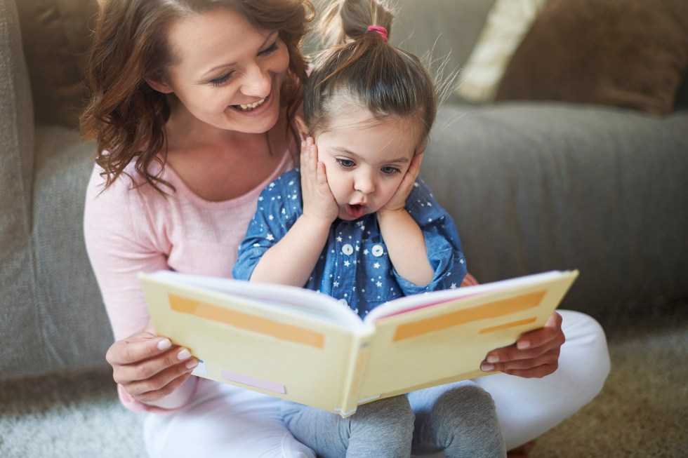 Mom teaching a toddler to read with an exciting and captivating book