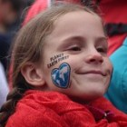 """Girl's face with """"Earth First"""" painted on her cheek"""