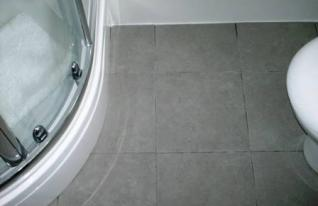 Grout Colour restored on a Ceramic Tiled Bathroom Floor by the Tile Doctor - Before Picture