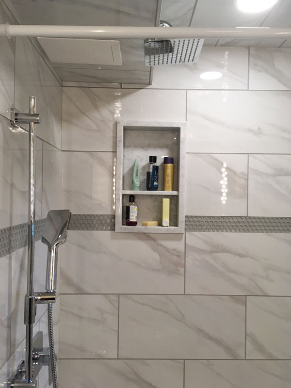 Marble Imitation Calacutta X and Element Mist Glass Penny Round Mosaic installed in a shower