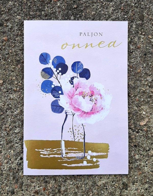 """Kaksiosainen onnittelukortti, jossa kannessa kukka lasipullossa ja teksti """"Paljon onnea"""""""
