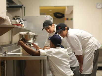 Three TCHS culinary students work on improving school lunch recipes.