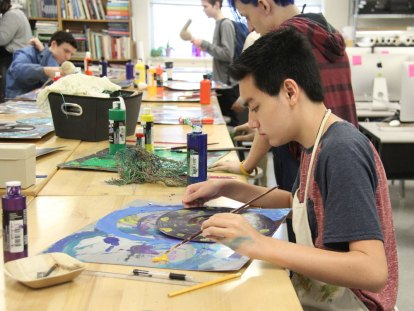 A Timber Creek art student paints a vinyl record to create a hand-made bowl.