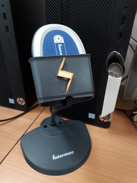 bar code scanner in front of a PC that has some trunking holding a desert spoon and a teaspoon for easy access