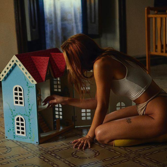 Belén Aguilera con una casa de muñecas y un top blanco/ Fuente: @Belen__Aguilera (Twitter)