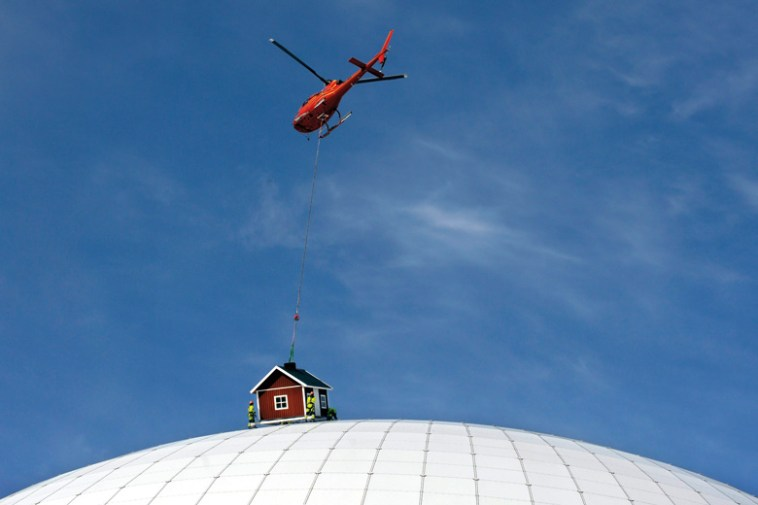 Helicopter lowers cottage onto Ericsson Globe Arena, Stockholm, Sweden
