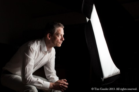 Tim Gander sits before a strobe softbox looking into the lit panel