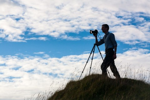 silhouette of photographer Tim Gander atop Cley Hill in Somerset with his camera on a tripod.