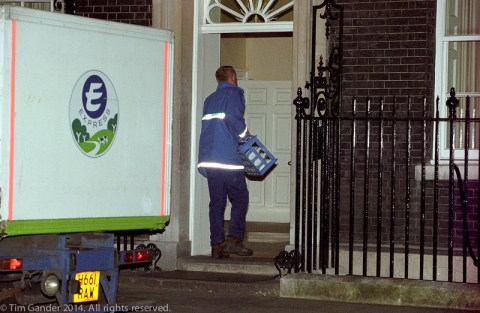 A milkman delivers a crate of milk to 10 Downing Street, London