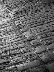 Angled detail view in black and white of cobbled street, Frome