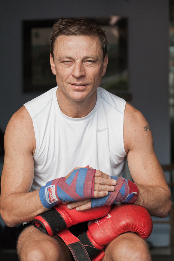 Portrait of Allan Meek looking to camera resting his boxing-gloved hands on a punch bag.